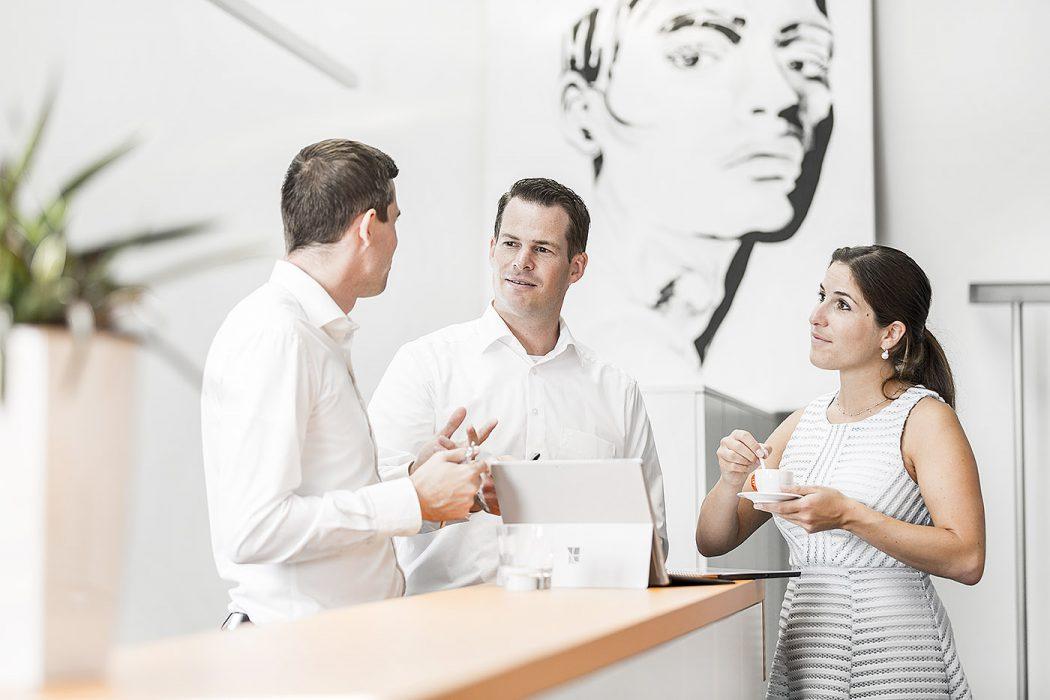Eine Frau und zwei Männer unterhalten sich bei einer Tasse Kaffee