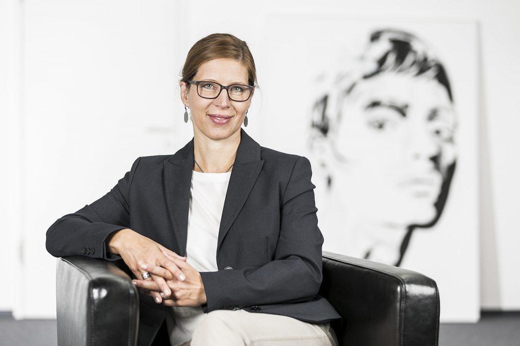 Geschäftsfrau sitzt auf einem Ledersessel