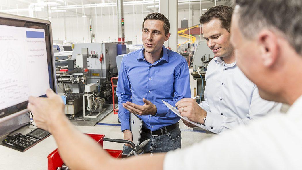 Unterhaltung dreier Männer in einer Fabrikhalle in Friedrichshafen