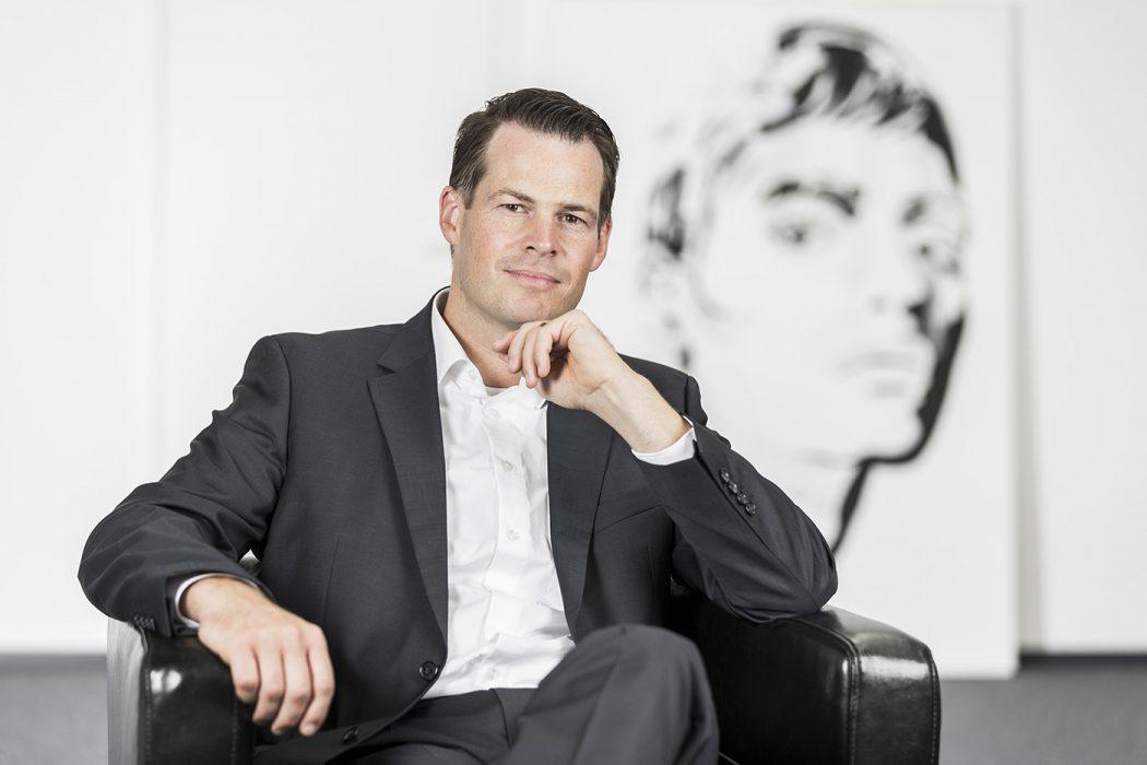 Portraitiert sitzend auf einem Ledersessel