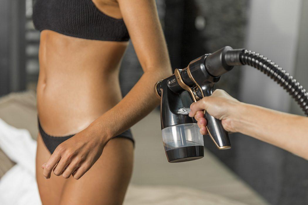 AURA Tanning Spray Frau wird eingesprüht