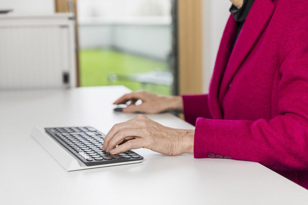 Frau im Büro an der Tastatur in ihrem Business Werbefotografie